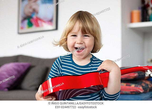 blonde two years old child with striped blue and white sweater inside home with red spanish little guitar in her hands laughing happy looking at camera