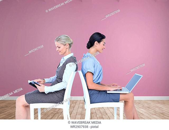 Businesswomen collaborating working back to back on chairs