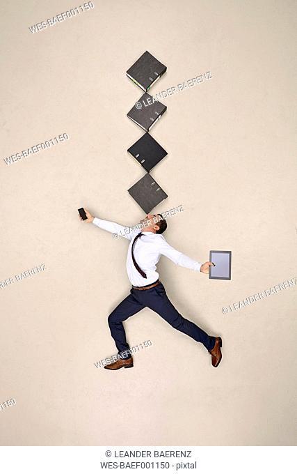 Businessman balancing folders on his nose