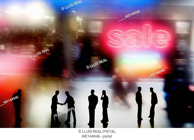 Digital composition of several silhouettes of unrecognizable people, closing a deal on a background of a notice of sale