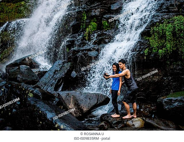 Couple taking selfie in front of waterfall, Ban Nongluang, Champassak province, Paksong, Laos