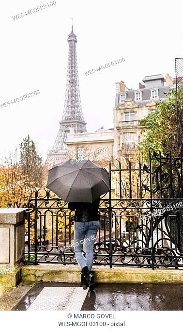 France, Paris, woman under umbrella with the Eiffel Tower in the background
