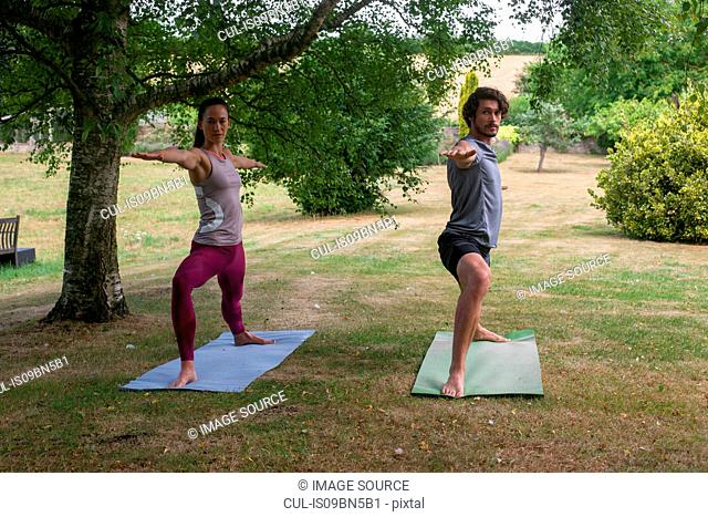Man and woman doing yoga in garden, practicing warrior pose
