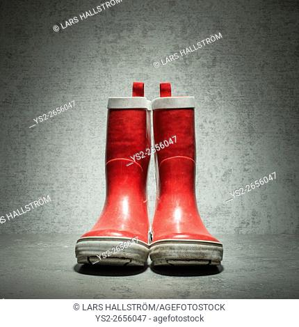 Red rubber boots in front of stone wall. Still life showing used waterproof rainboots