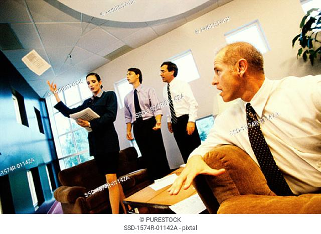 Businesswoman throwing documents with three businessmen watching