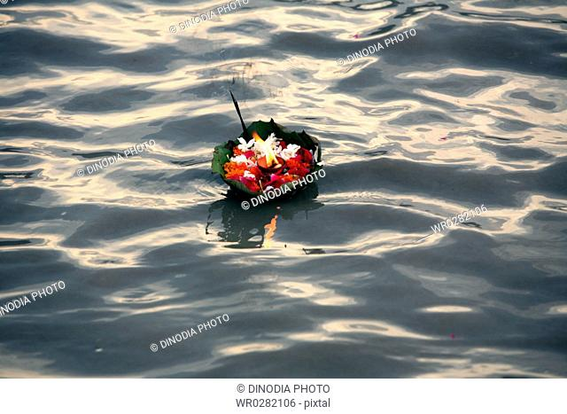Holy offering of flowers with agarbatti and diya in Ganga river , Rishikesh , Uttaranchal , India