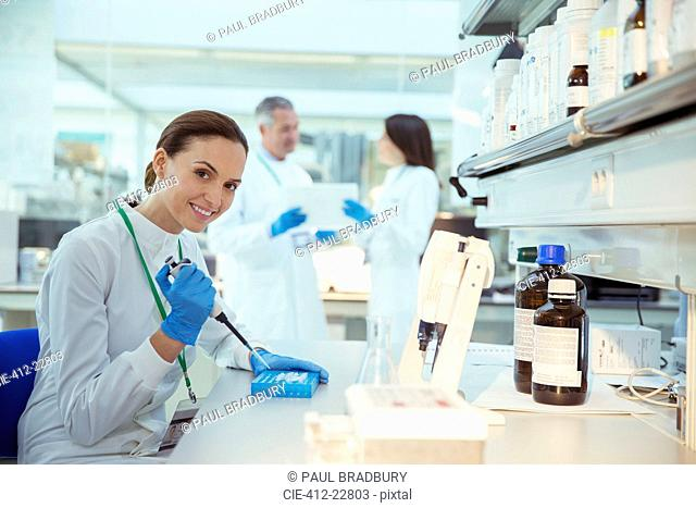 Scientist pipetting samples into tray in laboratory