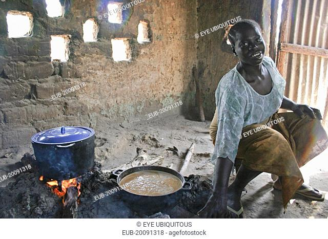 Young woman cooking a traditional Gambian dish of groundnut sauce called mafay over open fire in kitchen situated outside house with sunlight filtering through...