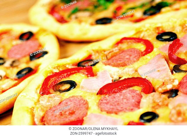 Pepperoni pizza with mushrooms, shrimps, olives and peppers