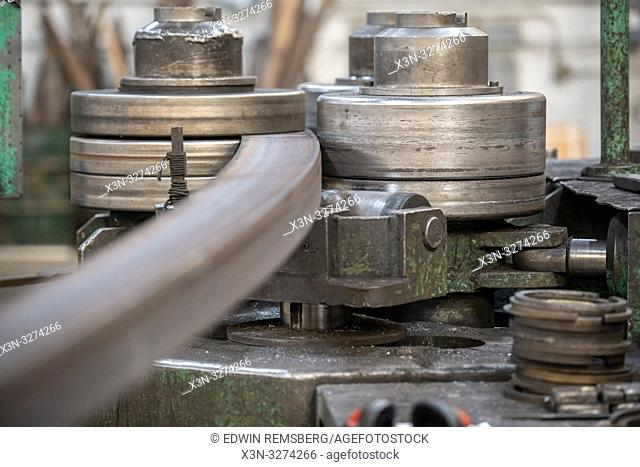 Machine rolling steel into a curve at metal bending shop, Dundalk, Maryland