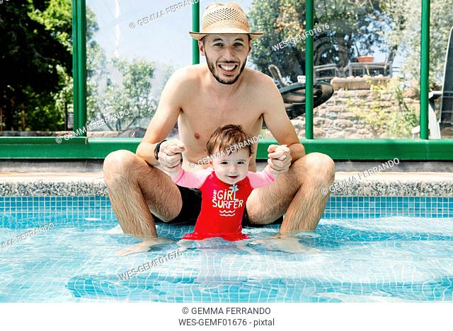 Happy baby girl in swimming pool with father