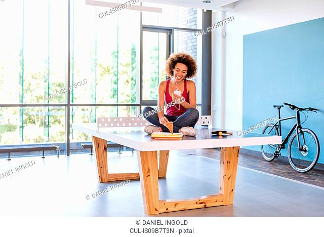 Young woman sitting on table tennis table listening to earphones and picking up pizza