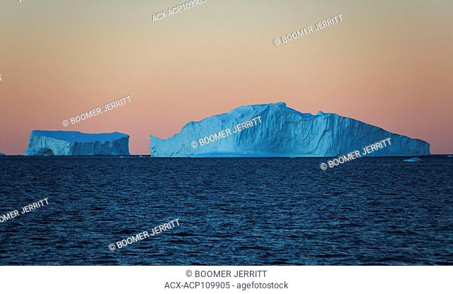 Twilight finds Icebergs floating in water against an orange cloudless sky near Fournier Bay, Antarctic Peninsula