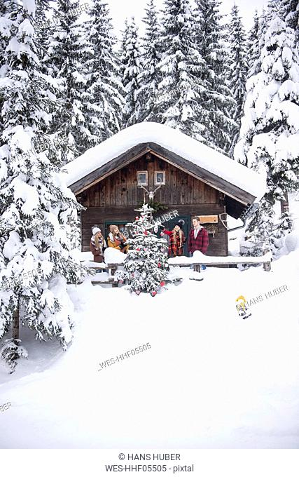Austria, Altenmarkt-Zauchensee, friends decorating Christmas tree at wooden house