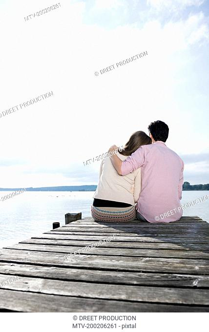 Couple hugging sitting lake jetty tranquil