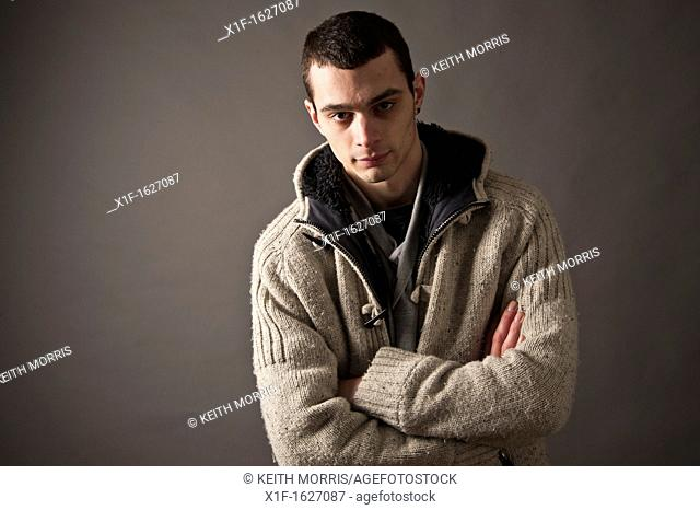 A slim thin slender late teen boy young man adult, with his arms folded UK