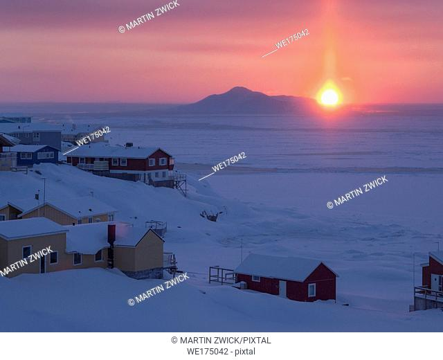 Sunset over icefjord and town. Town Ilulissat at the shore of Disko Bay in West Greenland, center for tourism, administration and economy