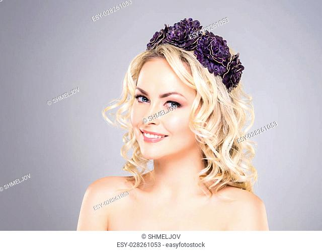 Beautiful, smiling, young lady wearing bijouterie over grey background