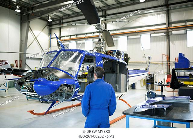 Helicopter mechanic in airplane hangar