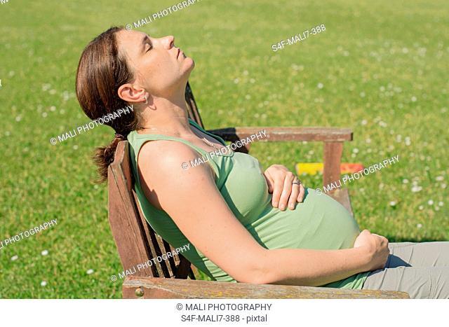 Schwangere Frau sitzt auf einem Gartenstuhl