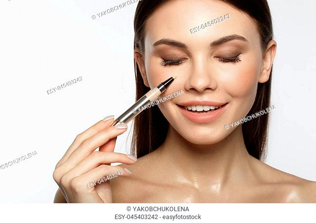 Close up portrait of happy girl putting on tone cream on her face. She is smiling with excitement. Isolated