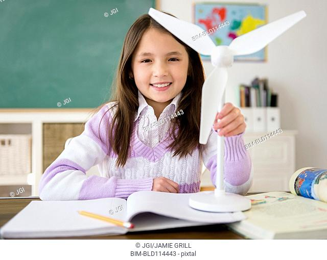Mixed race girl holding model wind turbine in class
