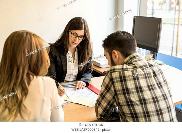 Clerk helping young couple filling in document