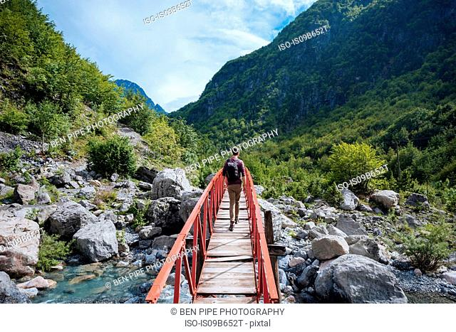 Rear view of man crossing bridge, Accursed mountains, Theth, Shkoder, Albania, Europe