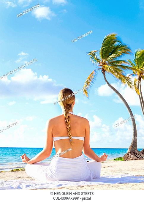Rear view of young woman practising yoga lotus pose on beach, Dominican Republic, The Caribbean