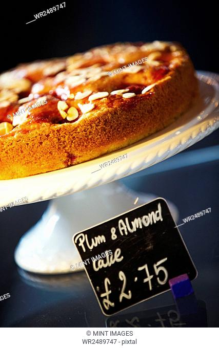 Specialist coffee shop. Plum and almond cake on a cake stand