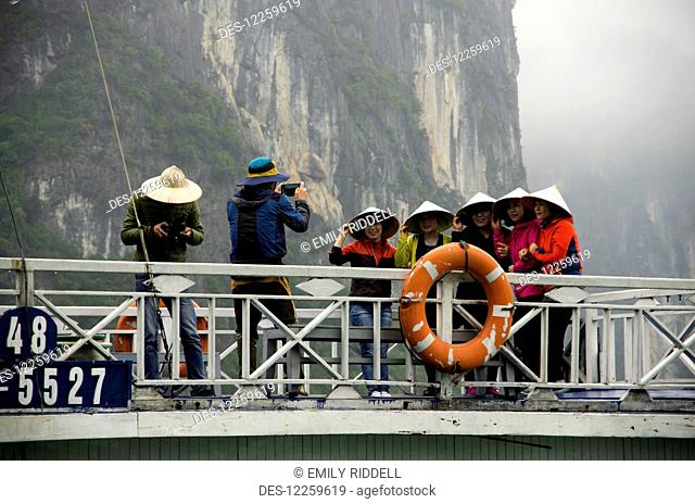 Five women wearing coolie hats line up for photo on top of passenger boat, and man looks at his camera; Halong Bay, Vietnam