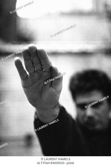 Man raising hand up, close-up, b&w