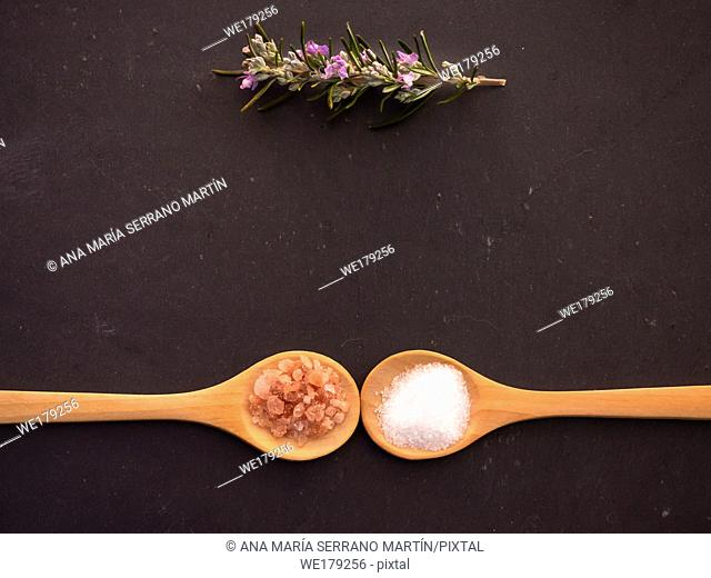 Wooden spoons with marine common salt and pink himalayan salt and a rosemary twig on a slate plate
