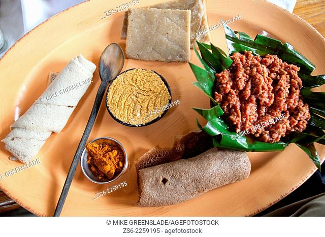 Traditional Ethiopian meal of 'Kitfo' served with cottage cheese, banana bread, chilli powder and injera