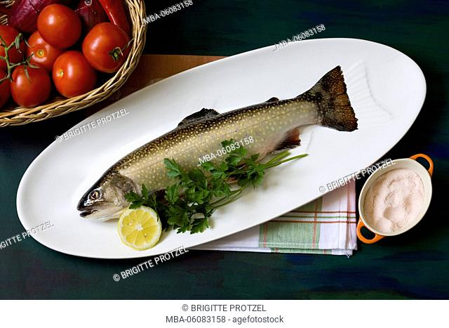 brook trout on fish plate with basket full of vegetables and salt