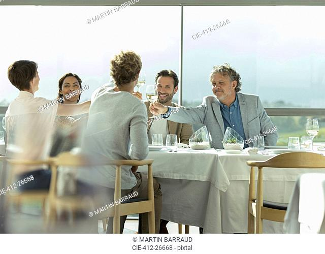 Friends toasting wine glasses at sunny restaurant table