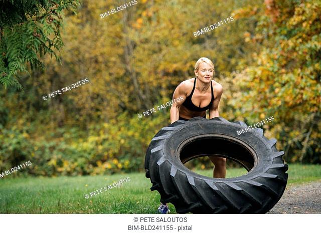 Caucasian woman lifting heavy tire in park