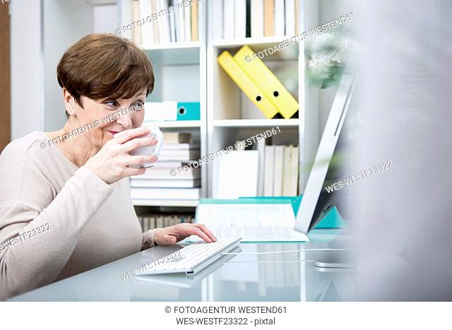 Senior woman working at computer with a cup of coffee