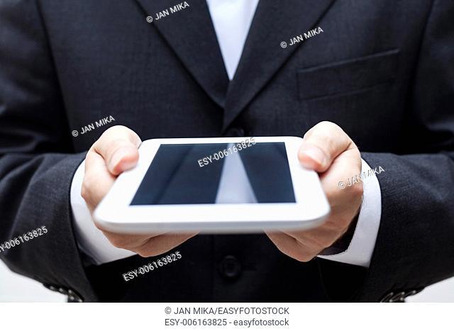 Detail of businessman holding digital tablet
