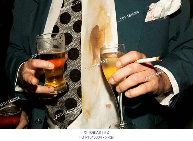 Midsection of a man holding drinks and cigarette at party