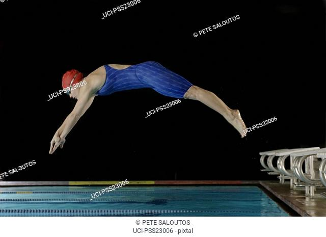 Female swimmer diving off starting block mid-air