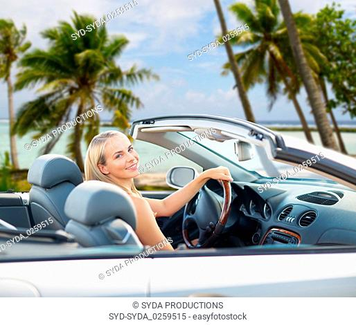 happy woman driving convertible car over beach