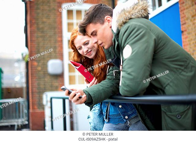Young male and female college students reading smartphone text on campus