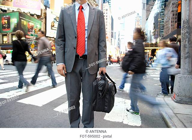 A businessman standing by a pedestrian crossing