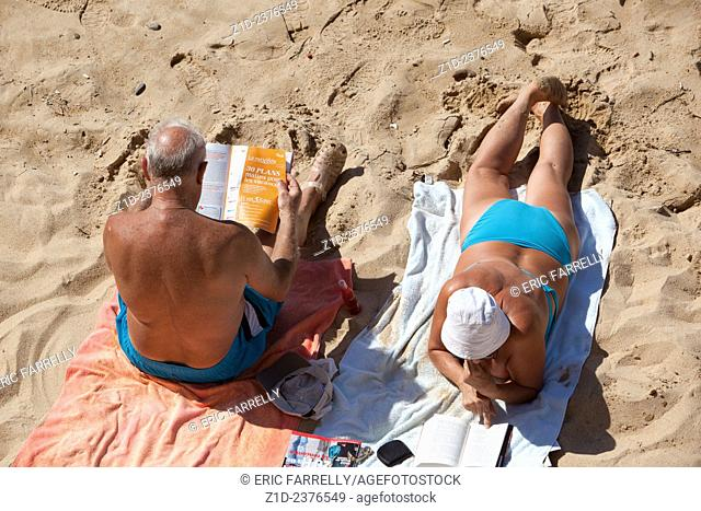 Couple enjoying reading on the beach at Ajaccio Corsica