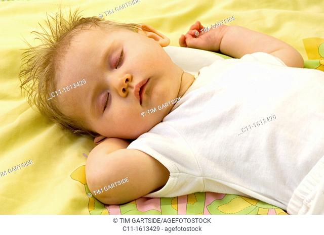 young baby girl 4 four months old sleeping in cot peacefully