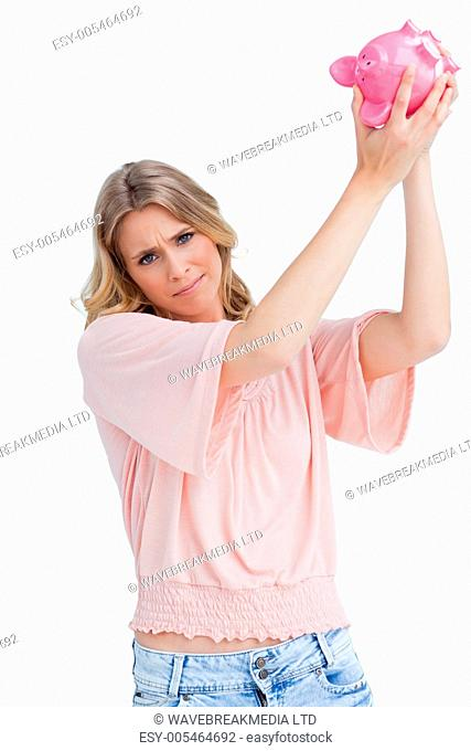 Disappointed woman holds a piggy bank up over her head