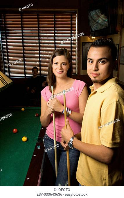 Portrait of young man and woman playing billiards