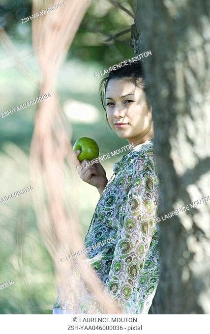 Young woman leaning against tree, holding apple