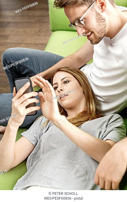 Young couple on couch in living room at home sharing cell phone